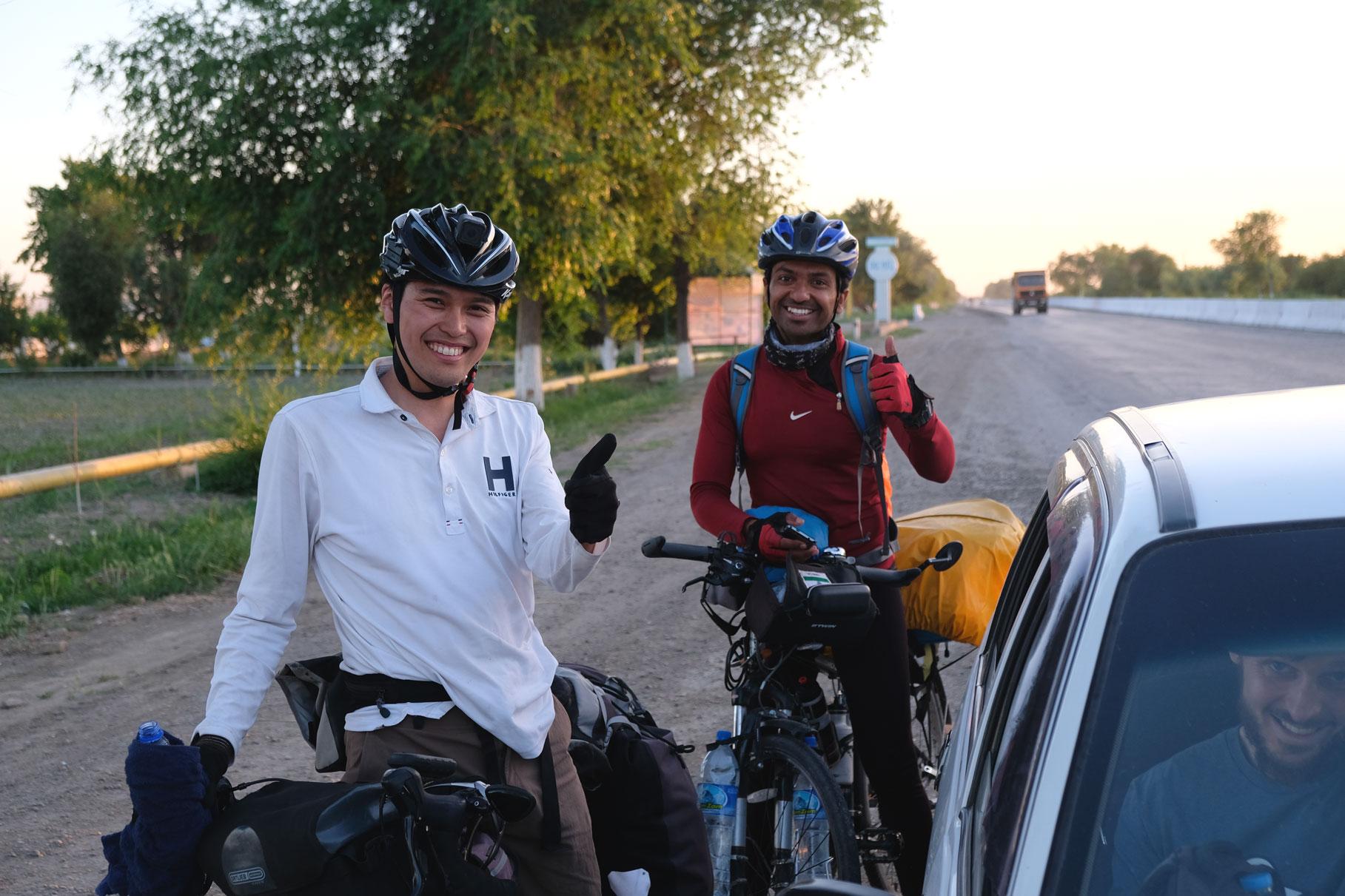 Ichiro und Jogesh auf ihren Fahrrädern neben einem Auto, in dem Sebastian sitzt