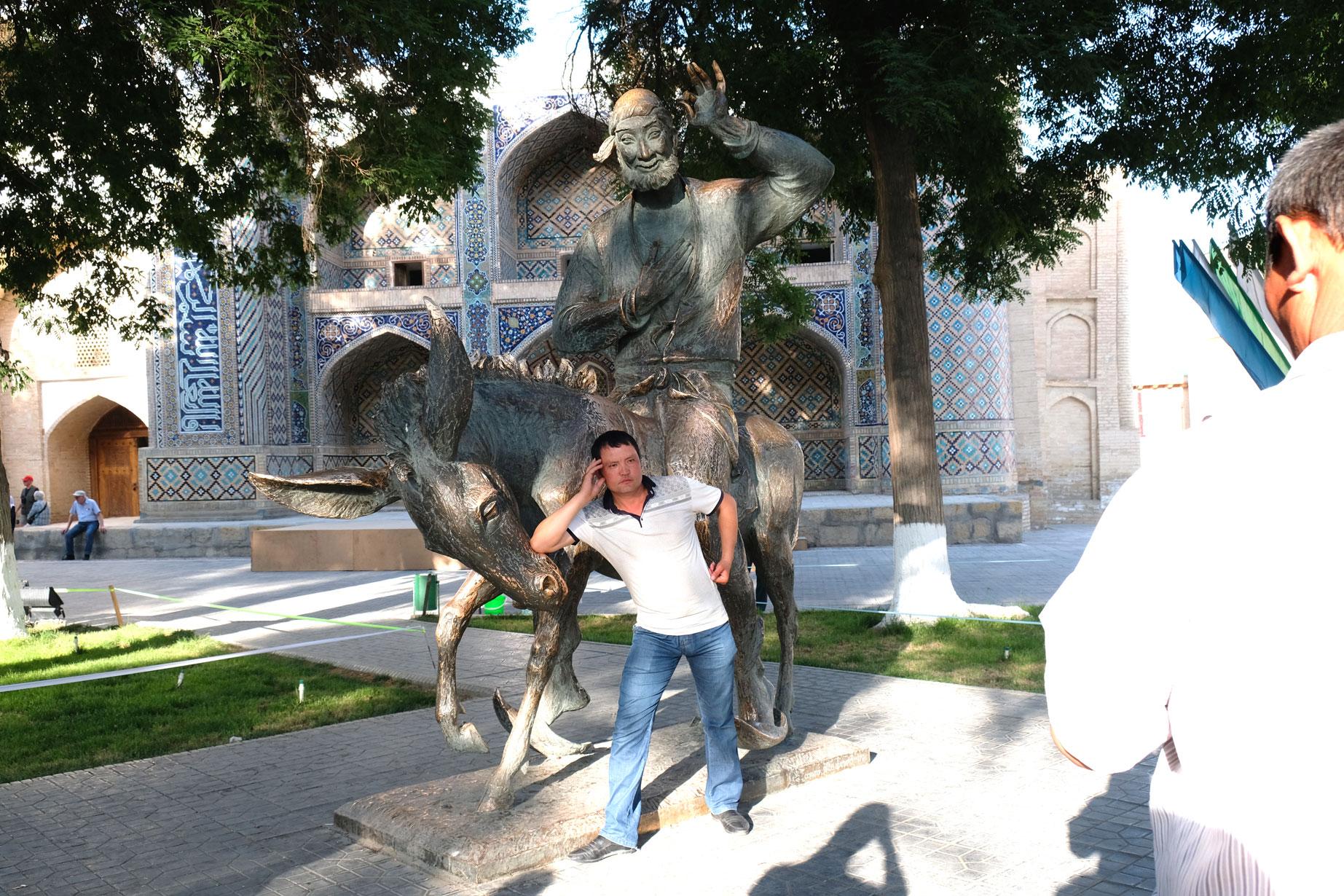 Ein Mann posiert vor einer Bronzestatue, die einen Esel und einen Reiter zeigt