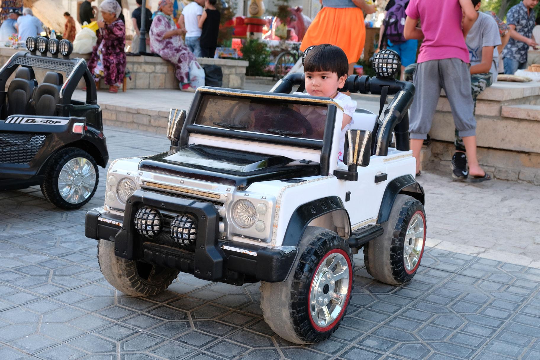 Ein Kleinkind in einem ferngesteuerten Miniaturauto