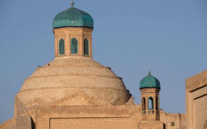 Sandsteinfarbene Gebäude mit türkisfarbenen Kuppeln
