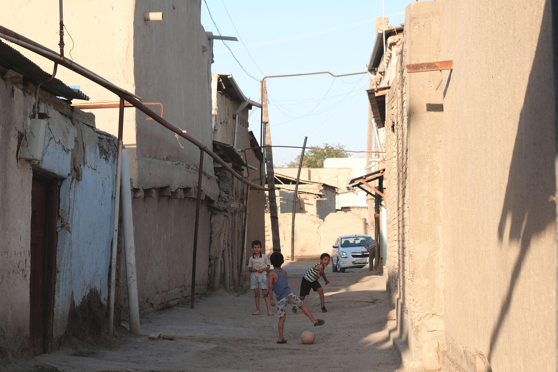 Drei Jungen spielen in einer Straße Fußball