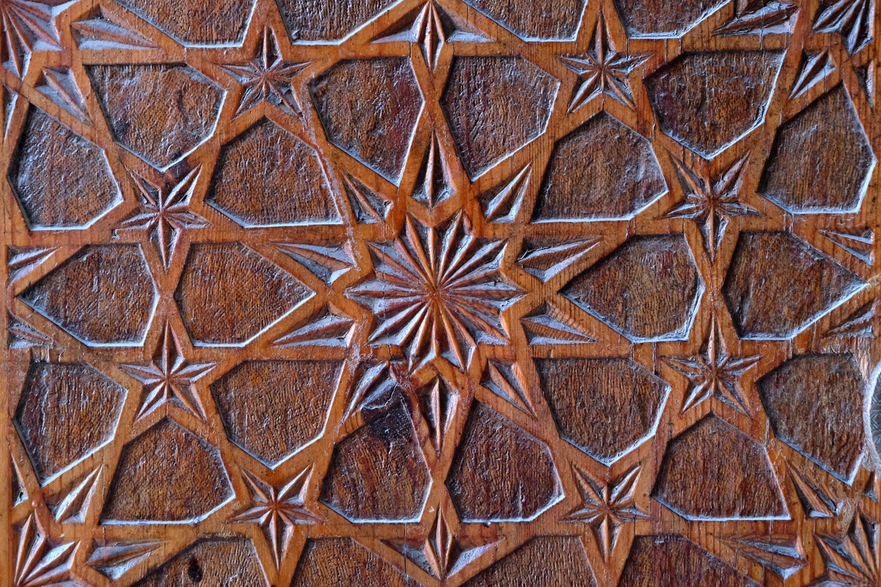Kunstvoll verziertes Eingangstor aus Holz