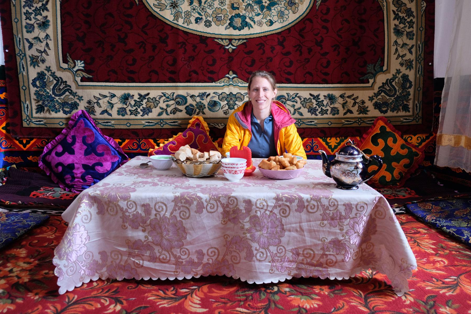Leo sitzt in einem dekorierten Wohnzimmer an einem Tisch auf dem Gebäck steht