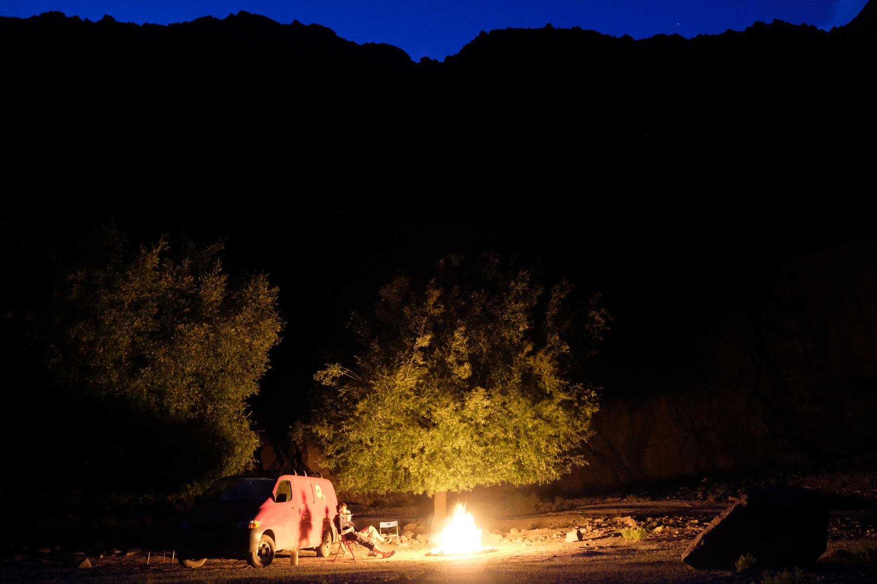 Ein roter Kleintransporter steht neben einem Lagerfeuer