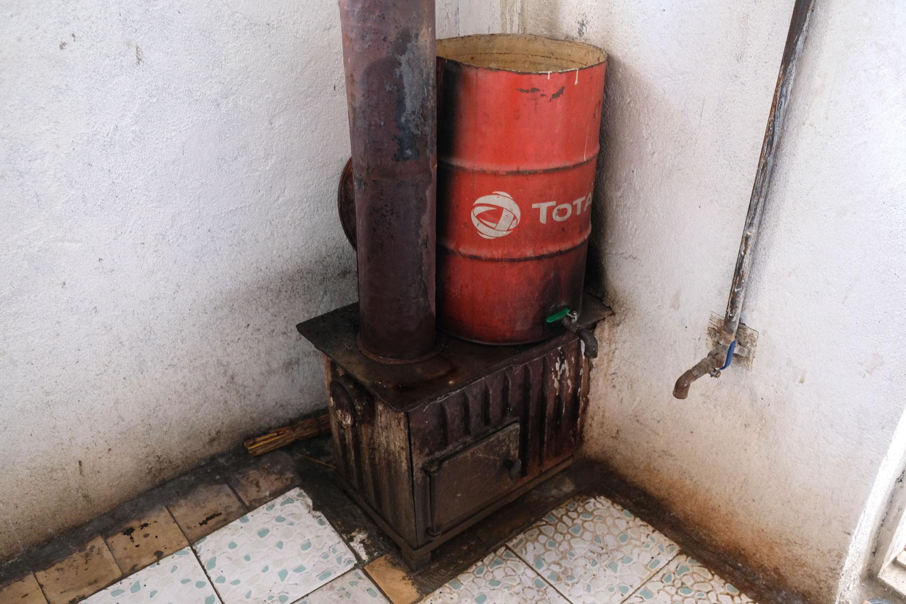 Ein Holzofen auf dem ein Fass steht. An der Wand verläuft ein Rohr mit Wasserhahn.