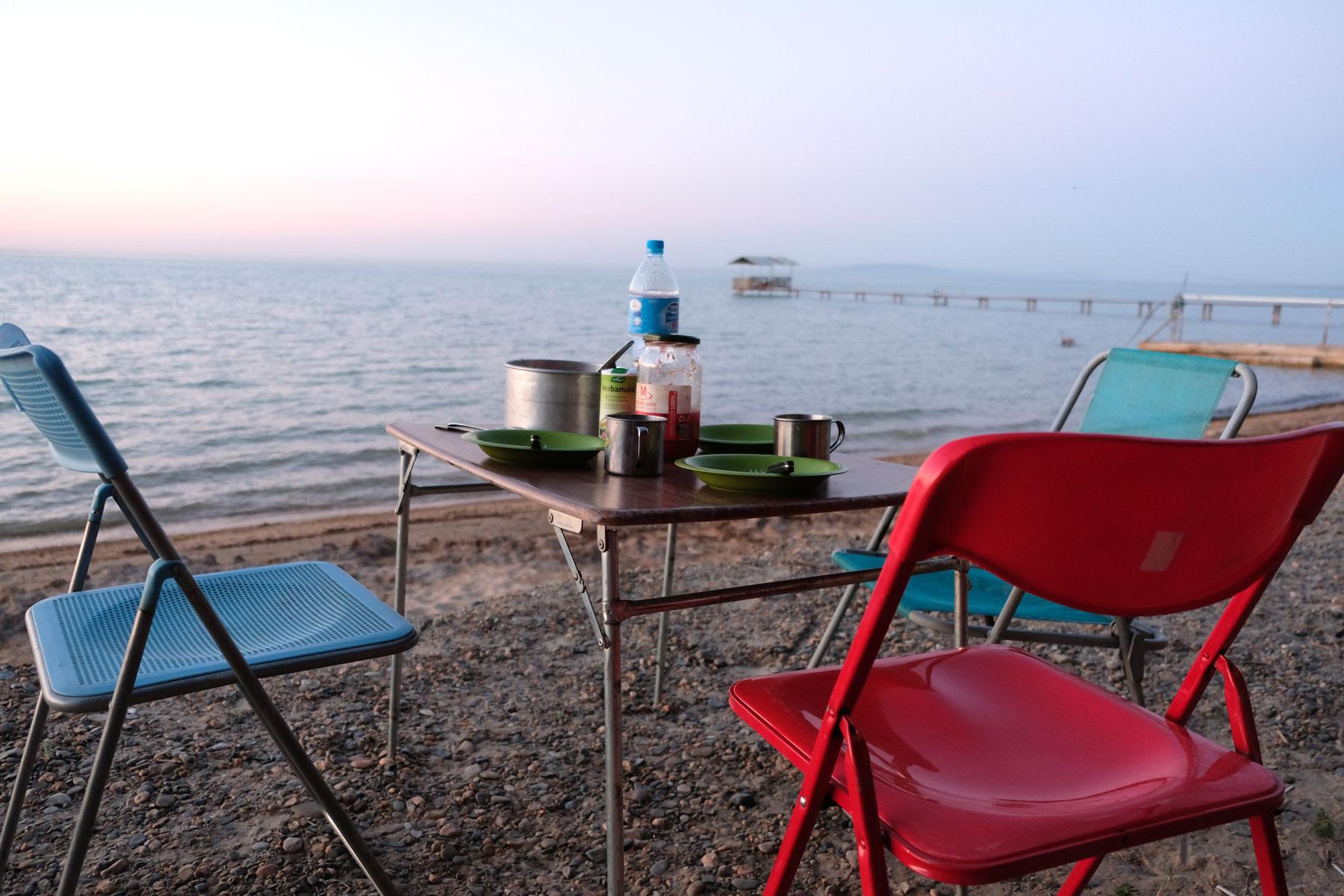 Campingstühle und ein Campingtisch am Ufer des Tudakul-Sees