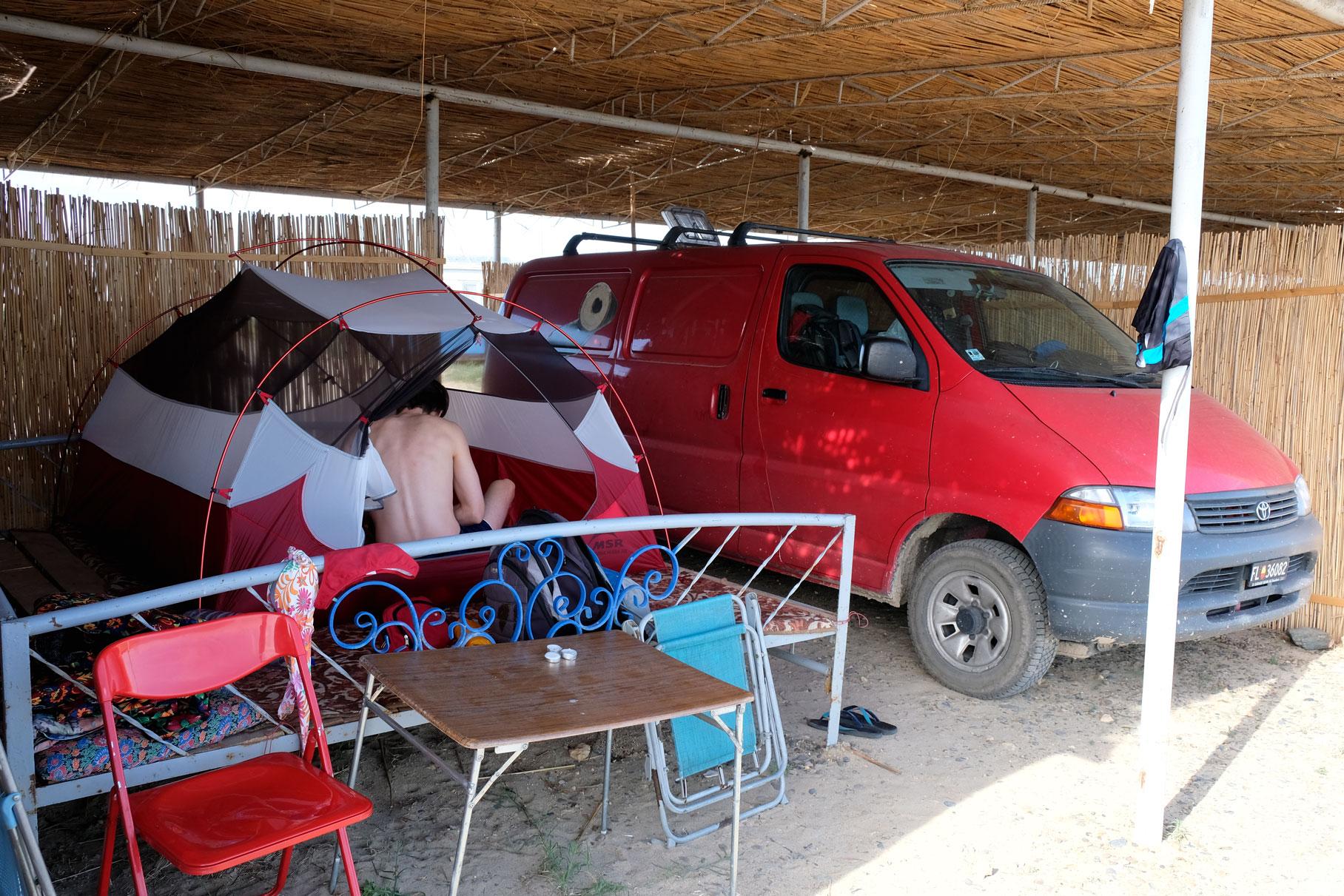 Sebastian sitzt in einem Zelt, das neben einem Kleintransporter steht