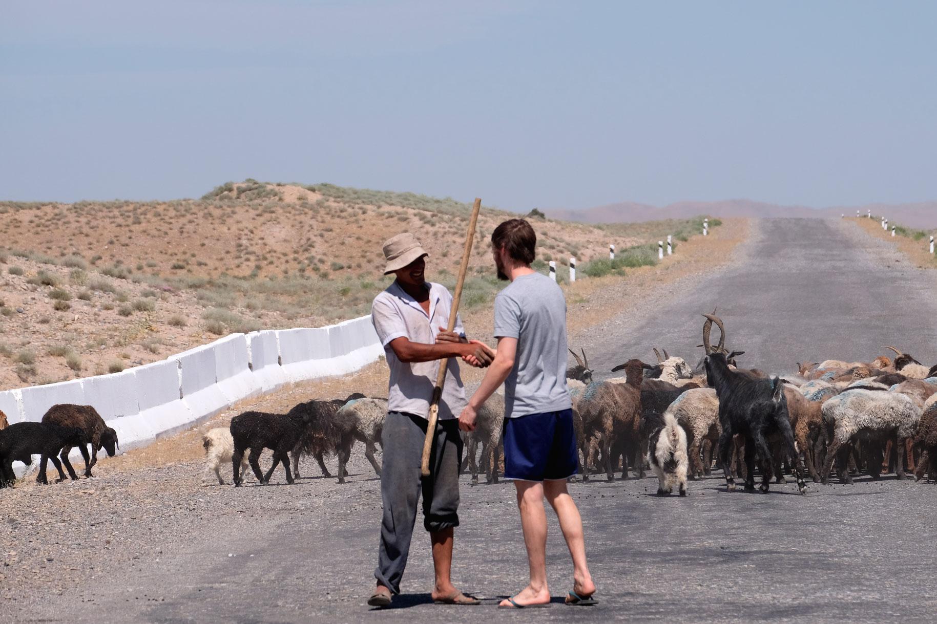 Sebastian begrüßt auf einer Straße einen Ziegenhirten per Handschlag