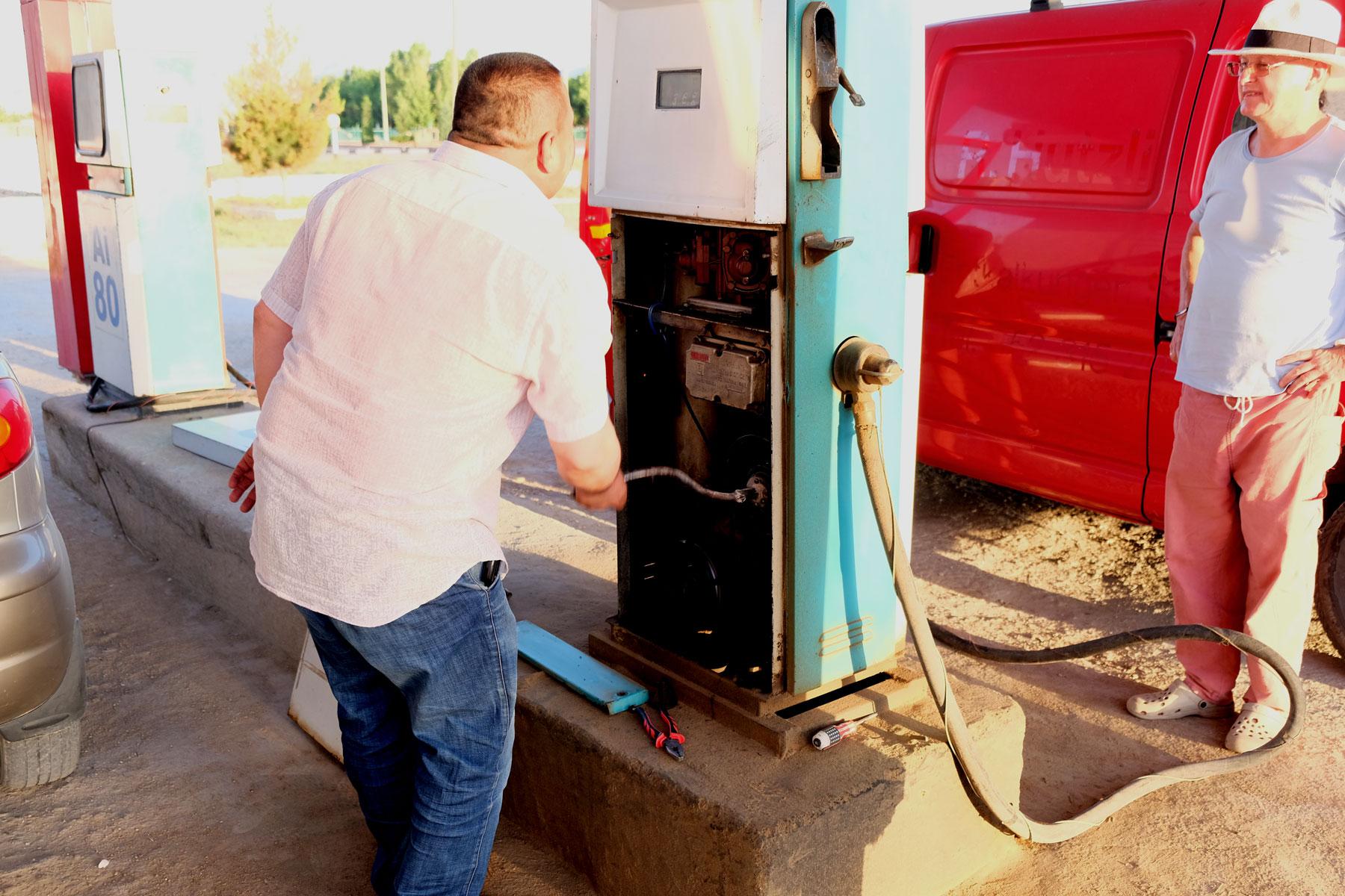 Ein Mann kurbelt an einer Zapfsäule einer Tankstelle
