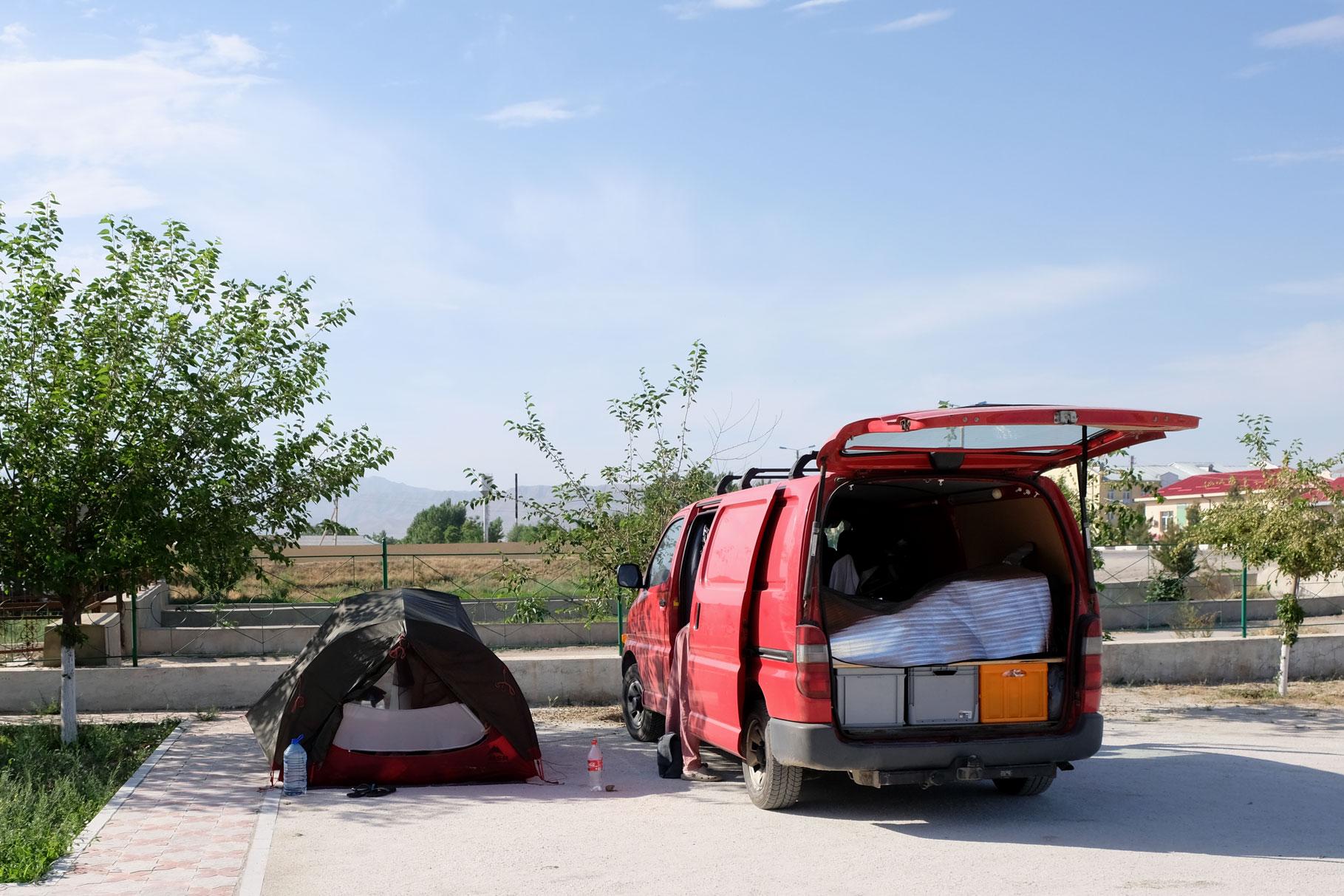 Ein Zelt steht neben einem roten Kleintransporter auf einem Parkplatz