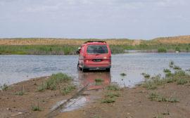 Ein roter Kleintransporter steckt in einem See fest