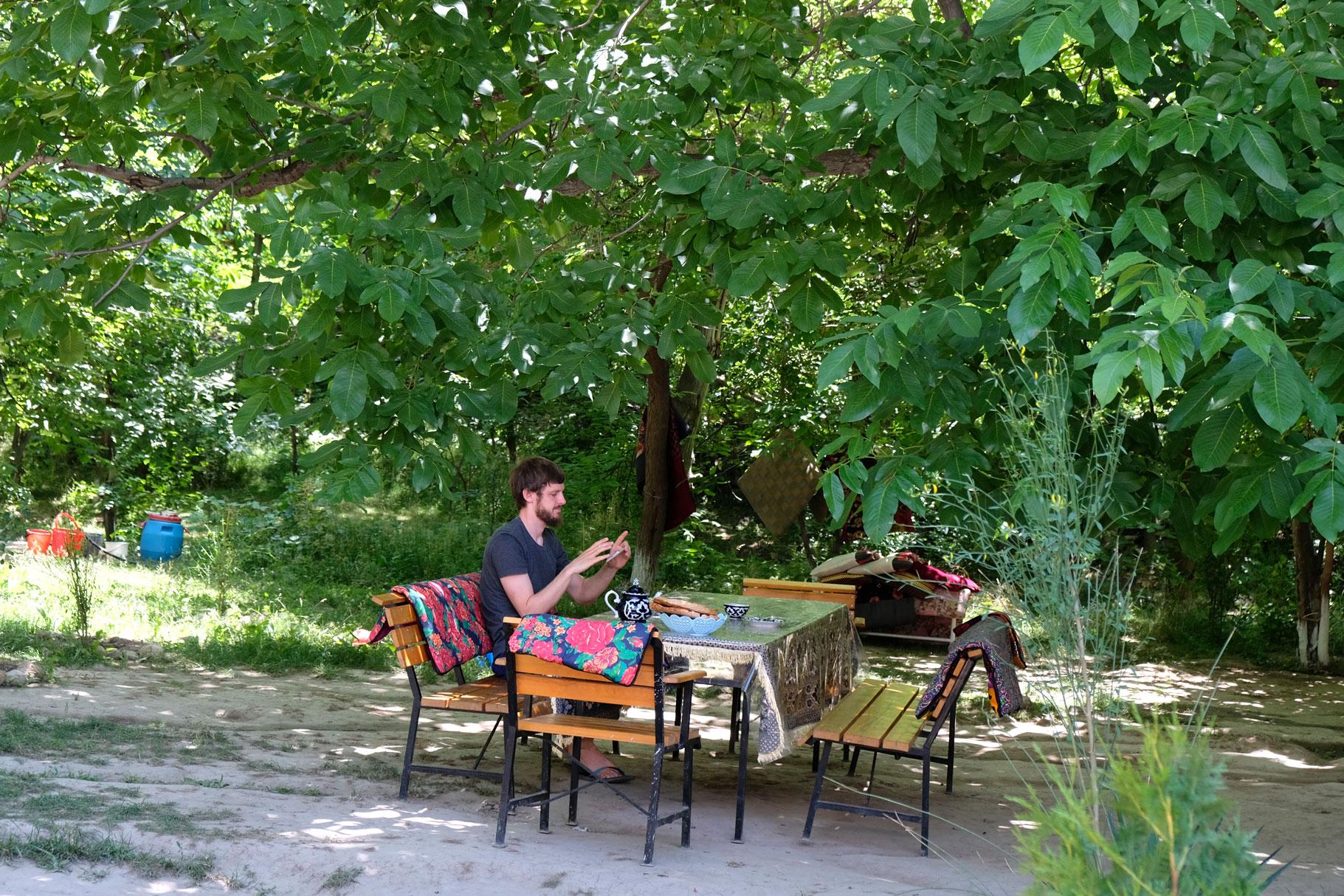 Sebastian sitzt mit Handy in der Hand an einem Tisch, der unter einem Baum steht.