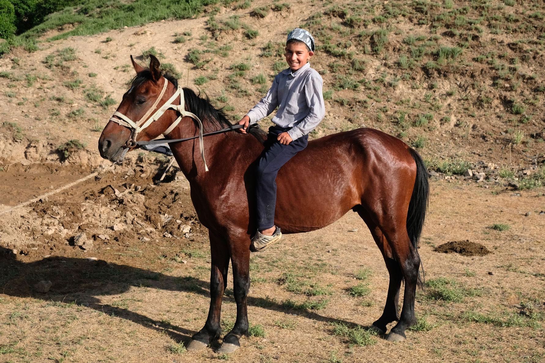 Ein Junge sitzt ohne Sattel auf einem Pferd