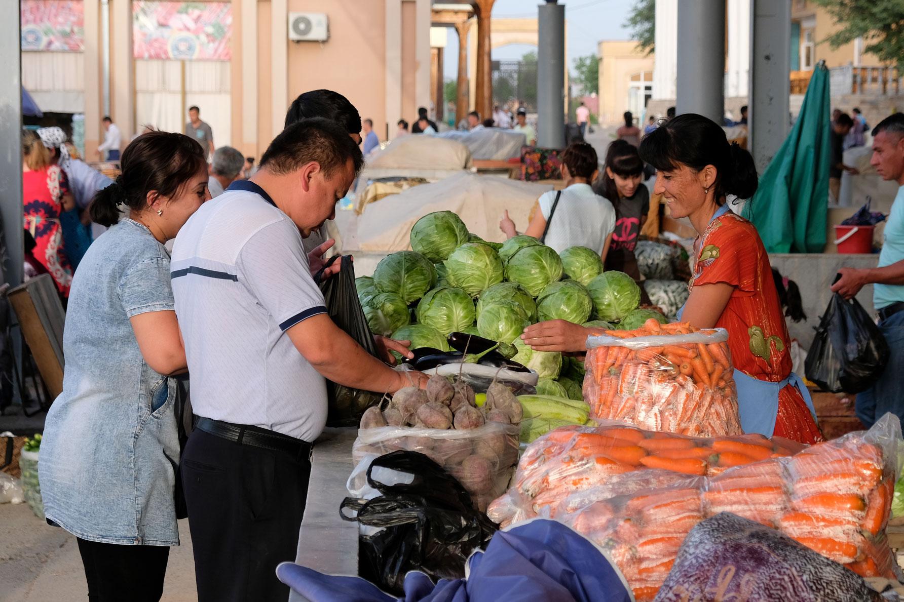 Menschen an einem Marktstand, an derm Kohl verkauft wird