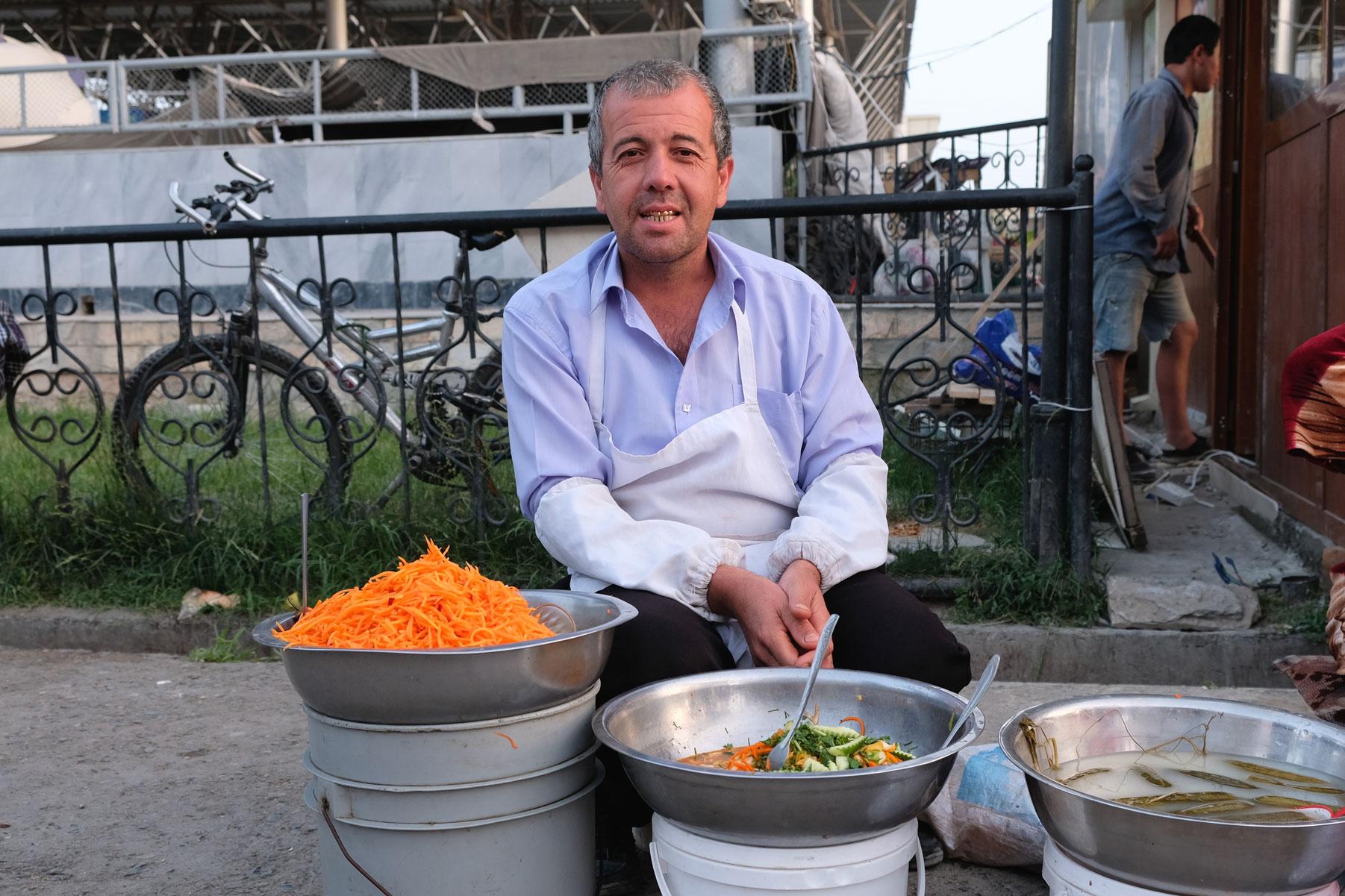 Ein Mann verkauft Salat auf dem Basar von Samarkand