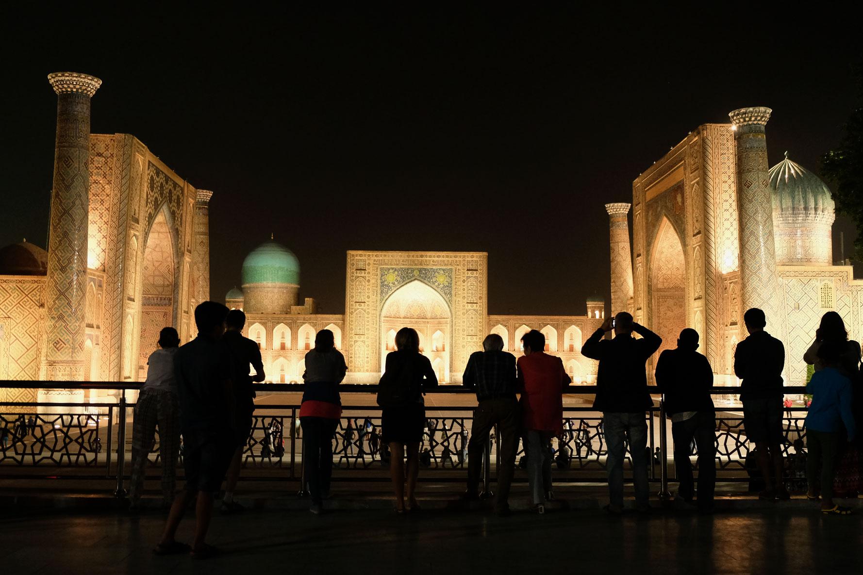 Menschen schauen von einem Geländer aus auf den Registan in Samarkand
