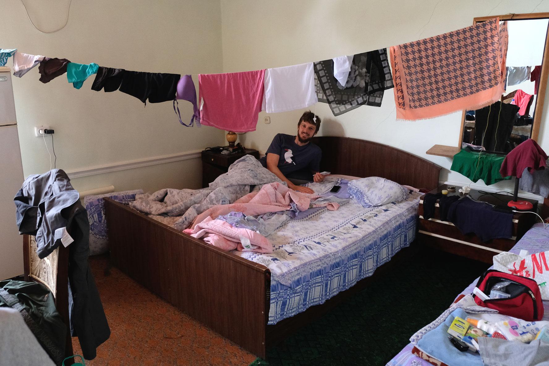 Sebastian liegt in einem Bett. Eine Wäscheleine ist durch das Zimmer gespannt.