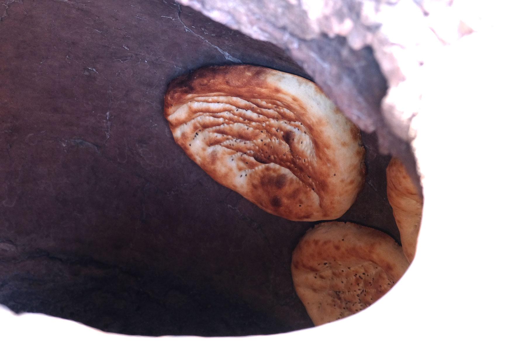 Brotlaibe kleben an der Wand eines Steinofens
