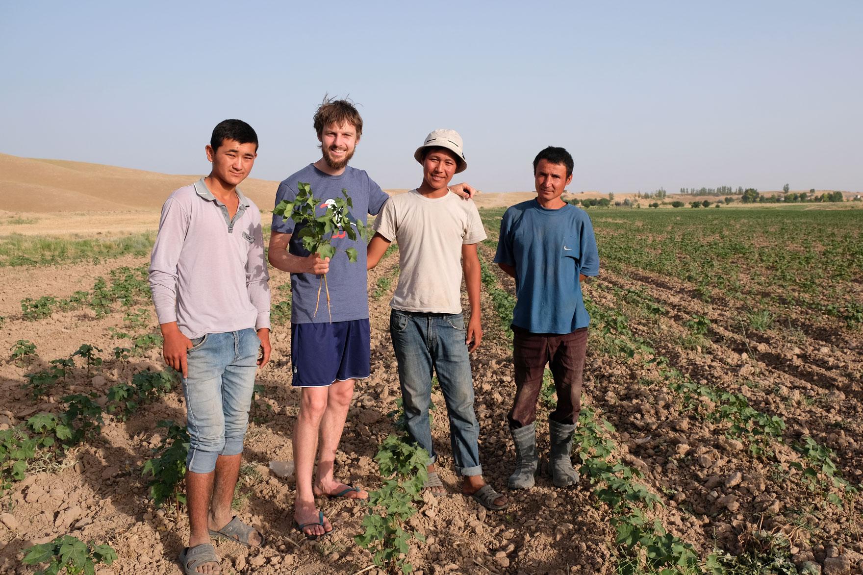 Sebastian mit drei Männern auf einem Baumwollfeld