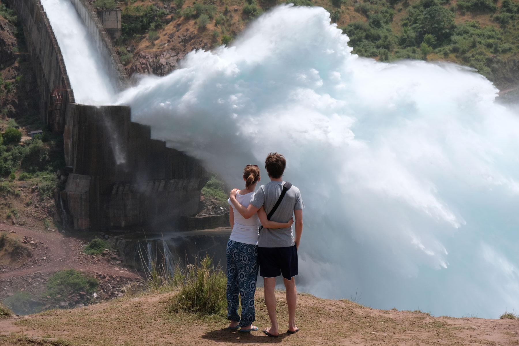 Leo und Sebastian vor einer gigantischen Wasserfontaine am Nurek-Stausee.