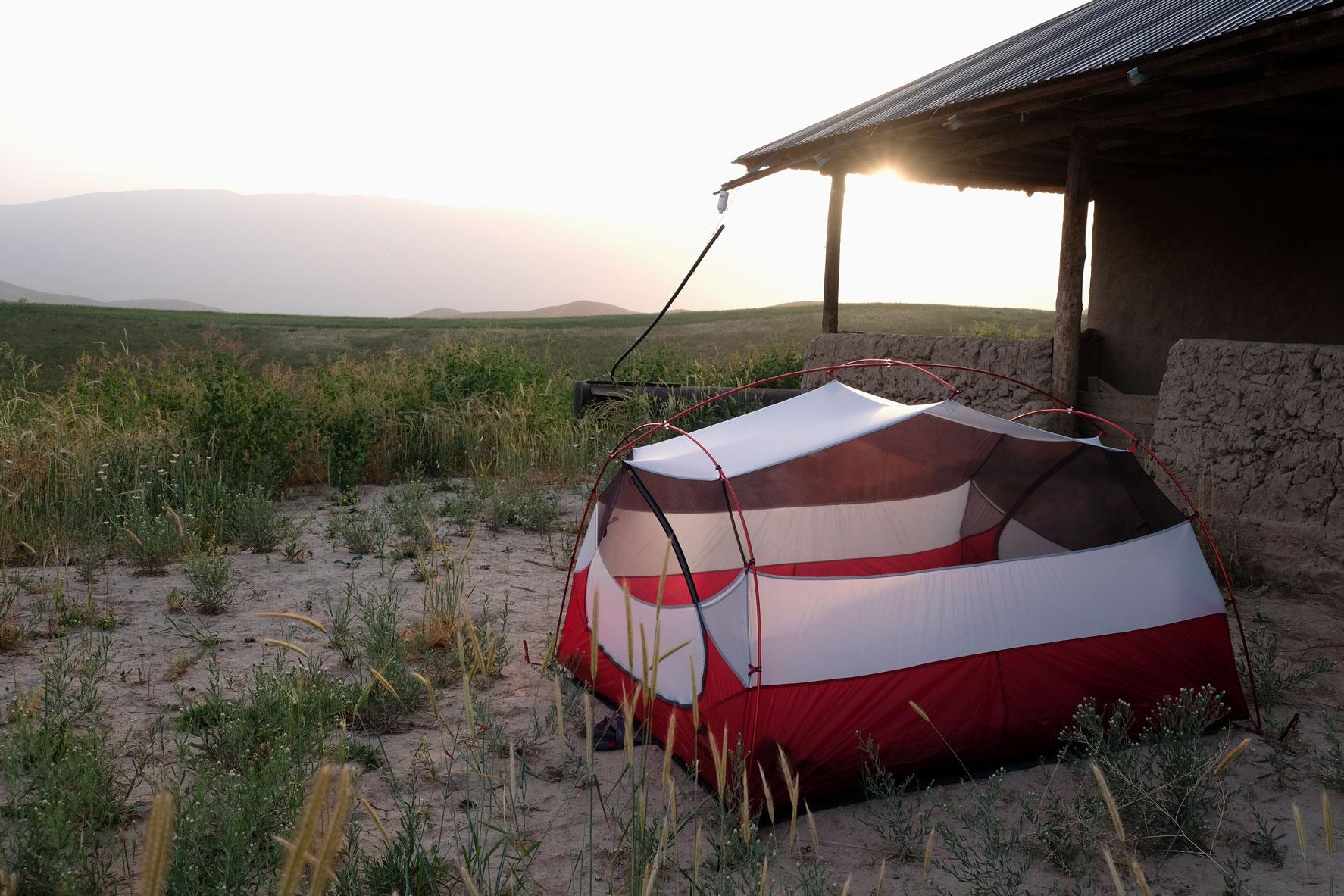 Ein Zelt steht neben einer Hütte auf einer Wiese.