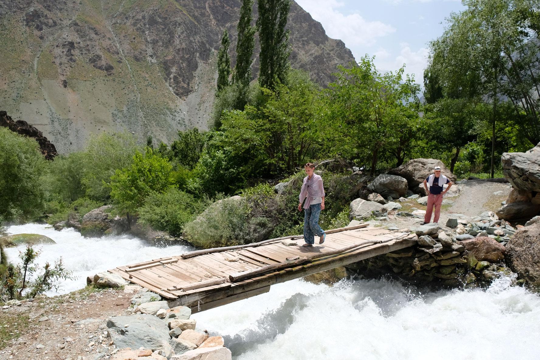Leo geht über eine Holzbrücke über einen reißenden Fluss.