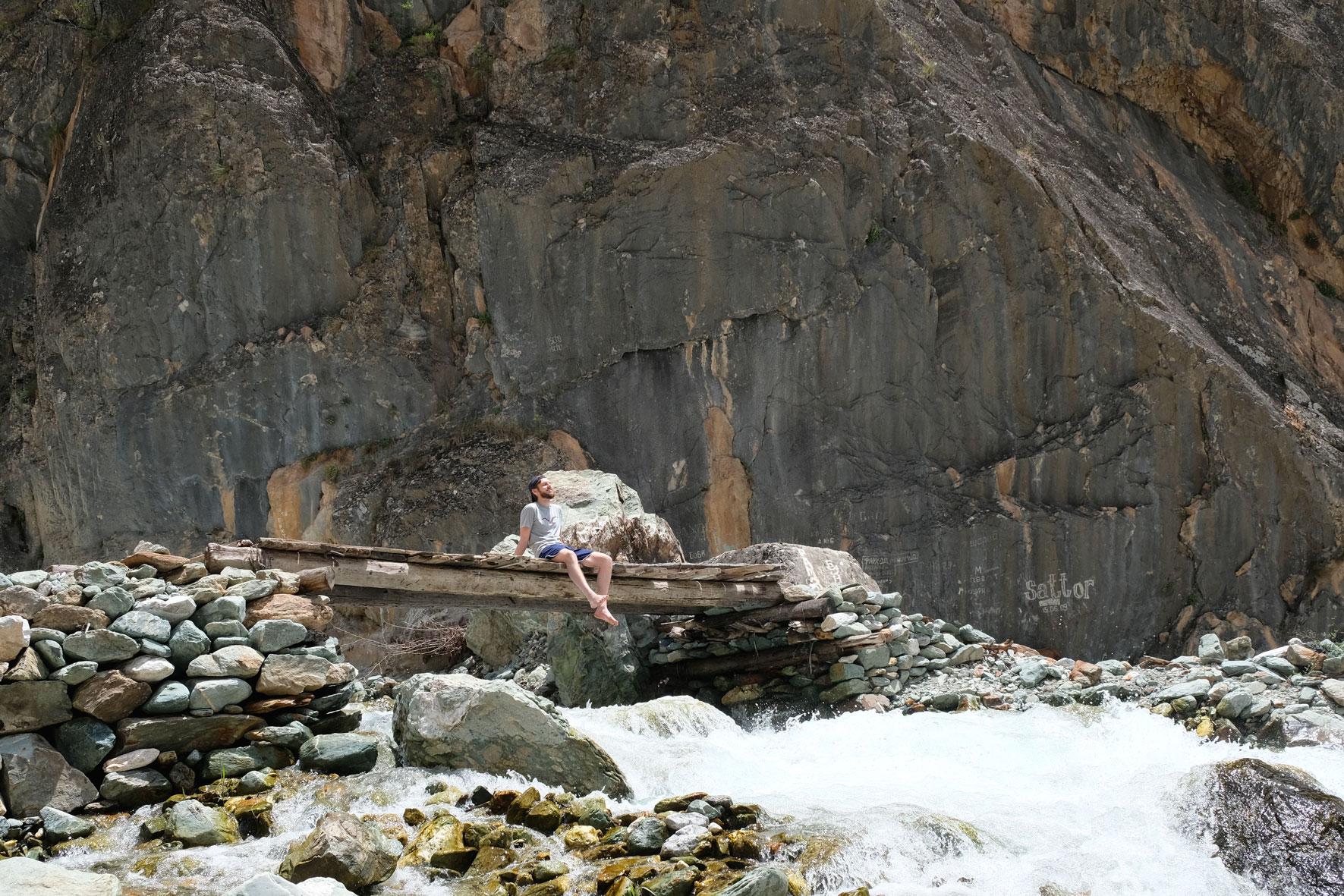Sebastian sitzt auf einer Holzbrücke, die über einen Gebirgsfluss führt.
