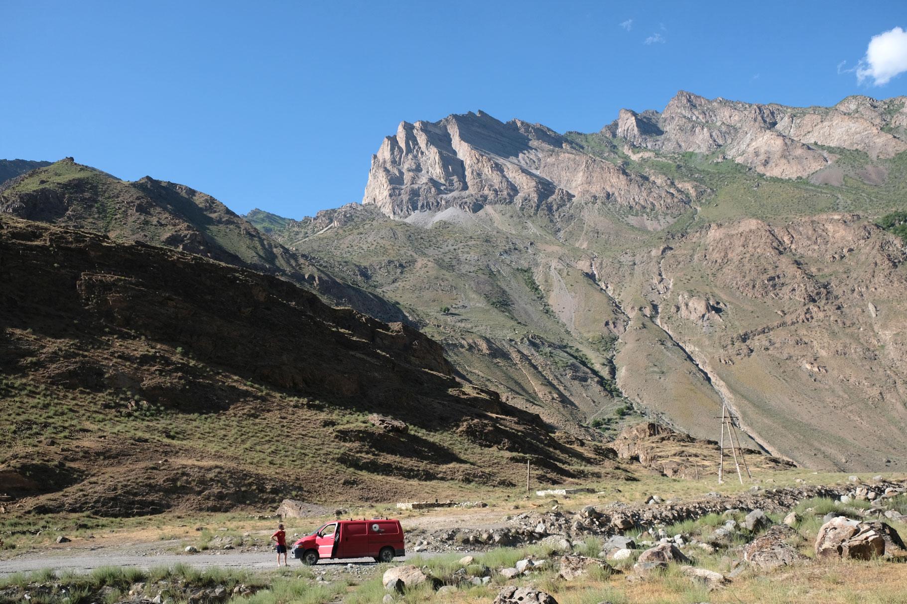 Sebastian neben einem roten Kleintransporter auf dem Pamir Highway.