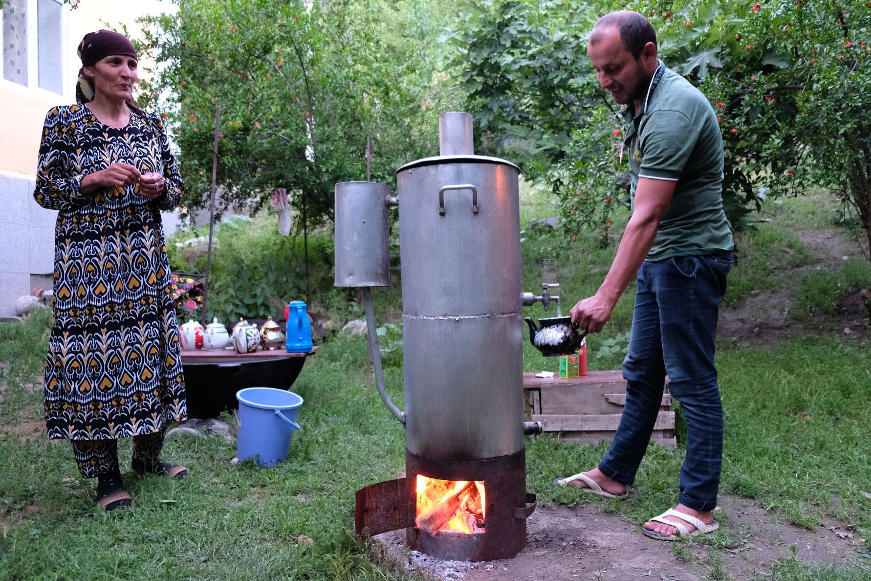 Ein Mann kocht Tee in einem übergroßen Samowar. Neben ihm steht eine Frau.
