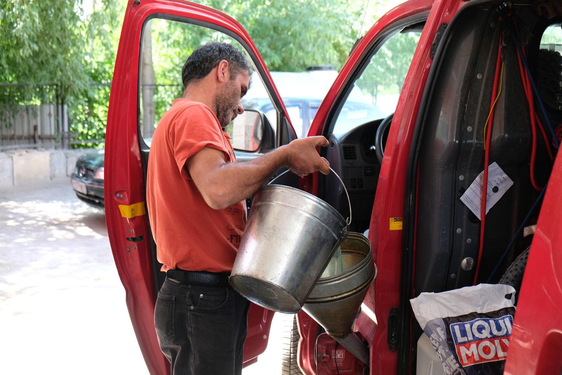 Ein Mann füllt mit einem Eimer über einen Trichter Benzin in den Tank eines Autos.