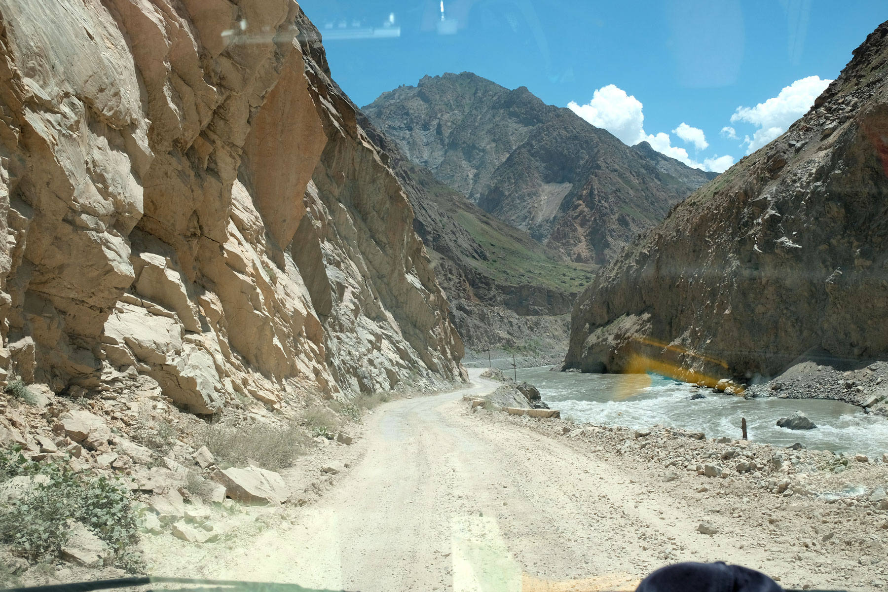 Schotterstraße neben einem Fluss auf dem Pamir Highway in Tadschikistan