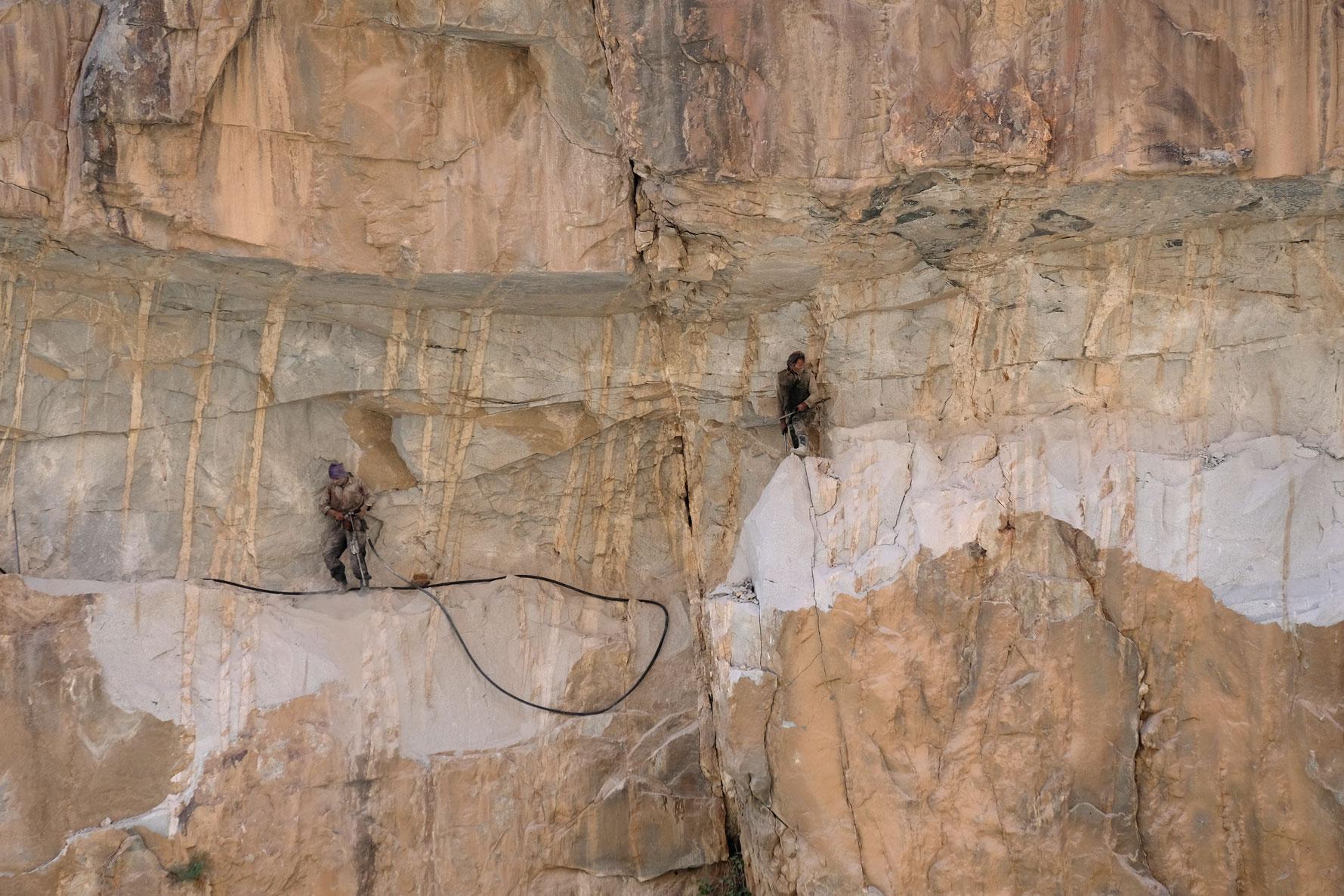 Zwei Männer arbeiten mit Presslufthämmern in einer Felswand.