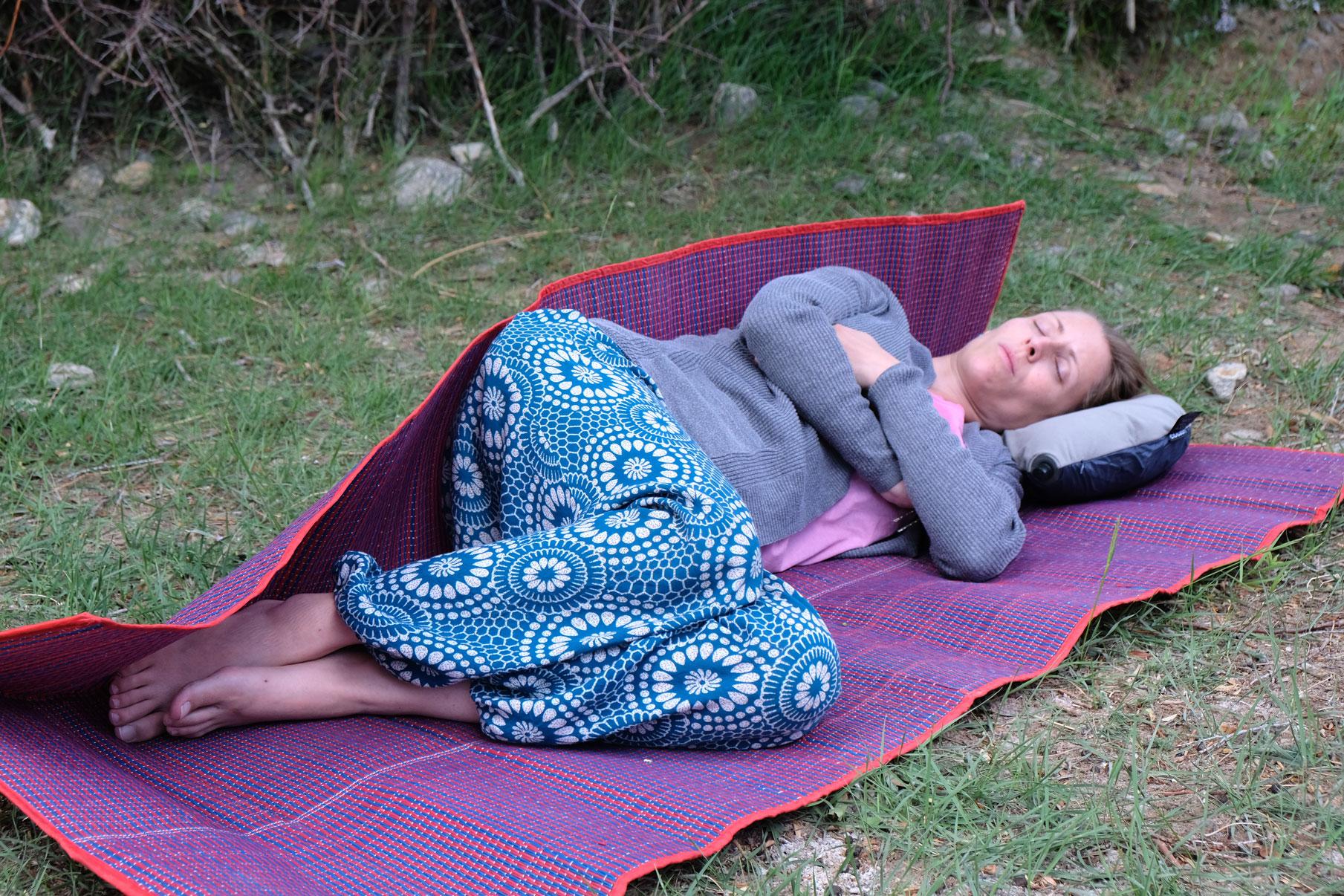 Leo schläft auf einer Isomatte, die auf einer Wiese liegt.