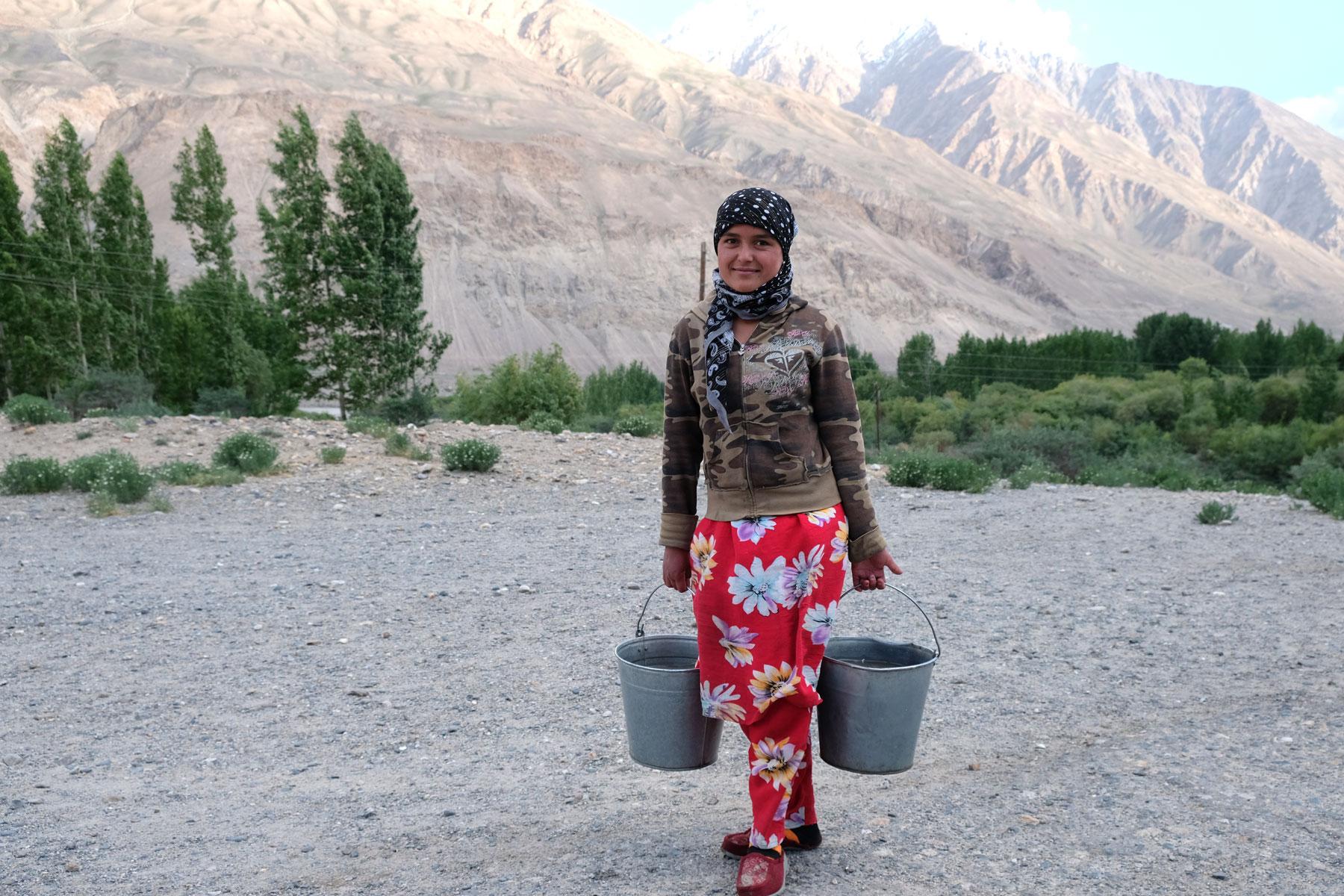 Ein tadschikisches Mädchen trägt zwei Wassereimer.