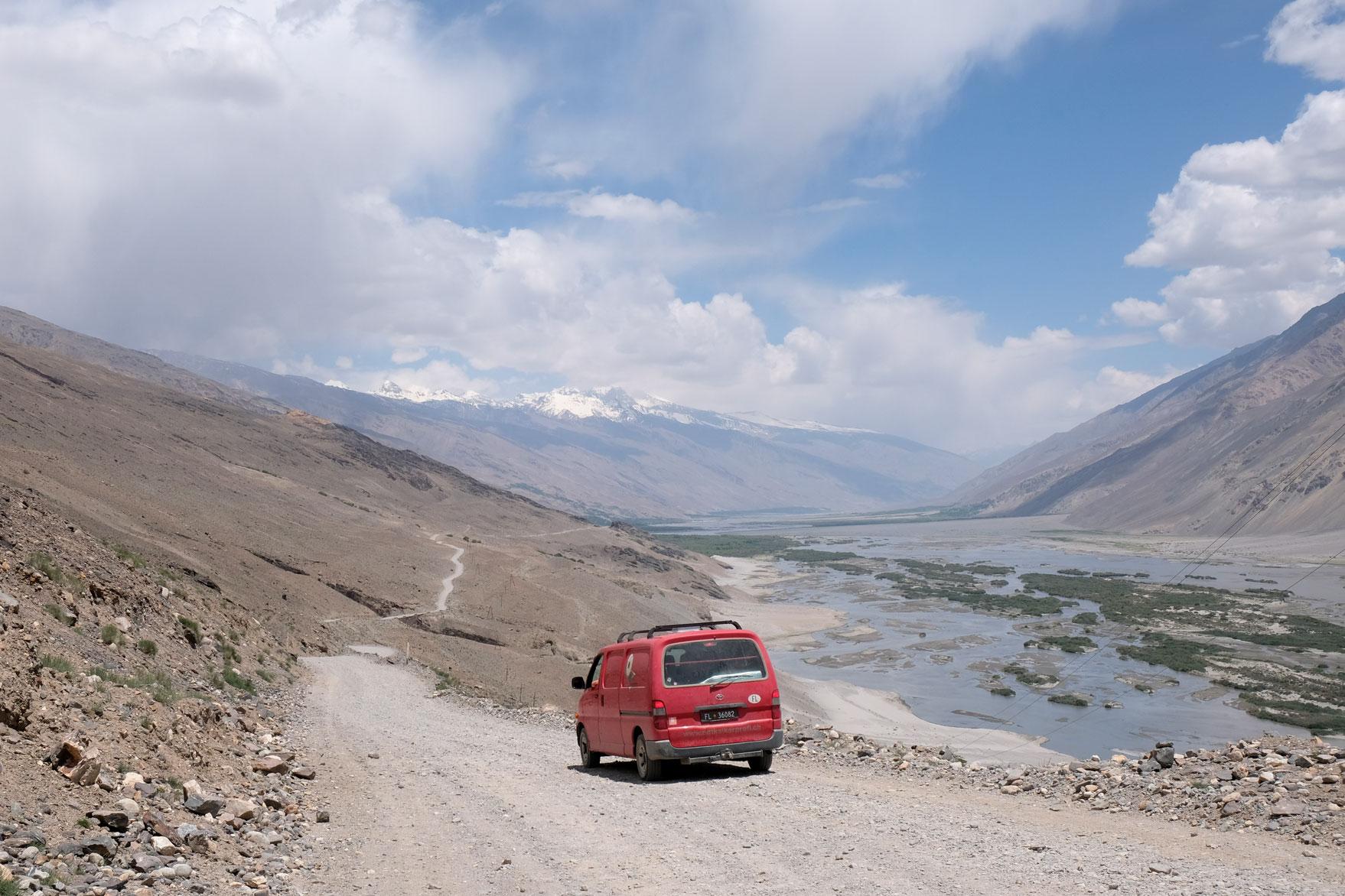 Ein roter Kleintransporter auf einer Schotterstraße auf dem Pamir Highway.