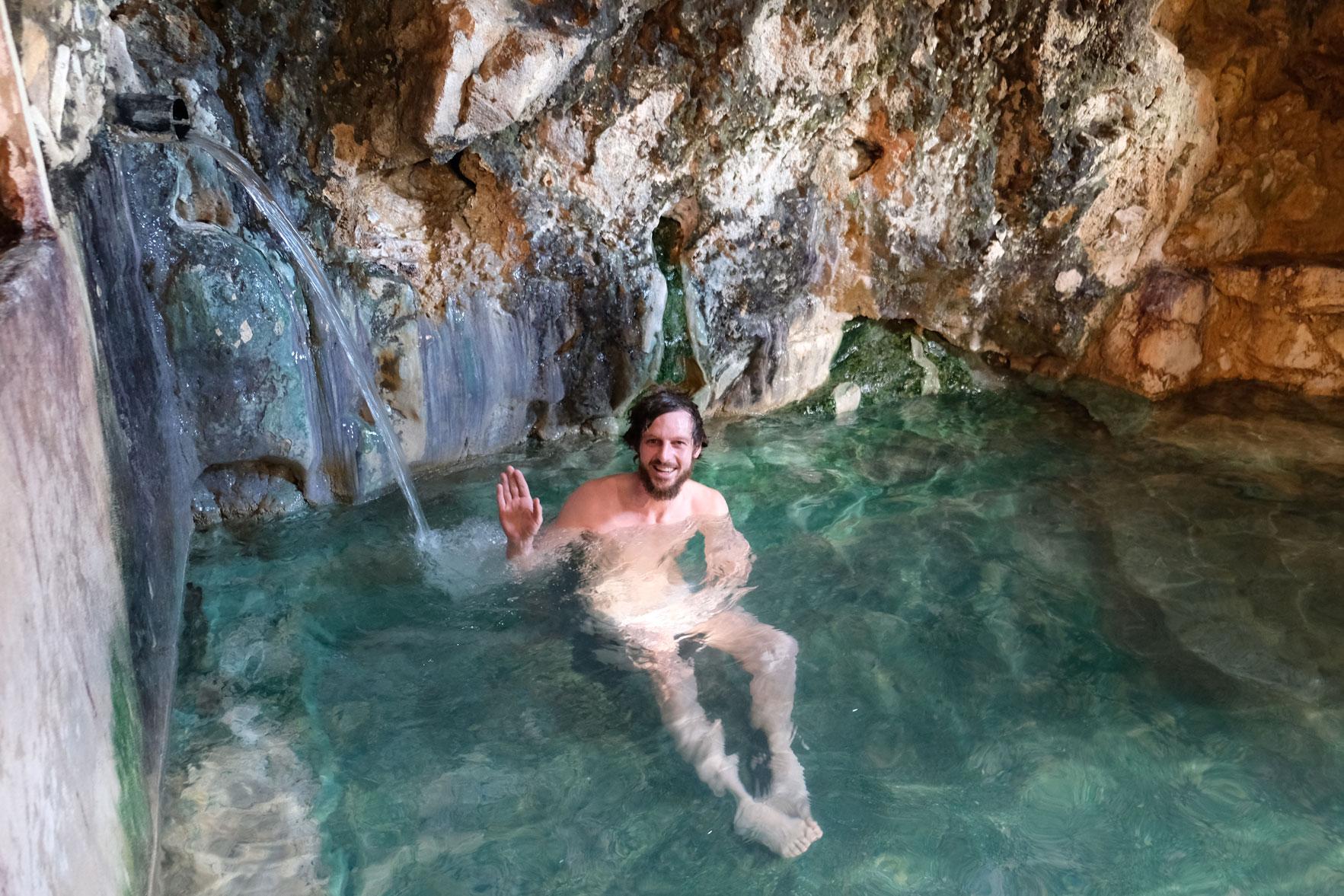 Sebastian sitzt nackt in einem Wasserbecken der Bibi Fatima Thermalquellen und winkt.