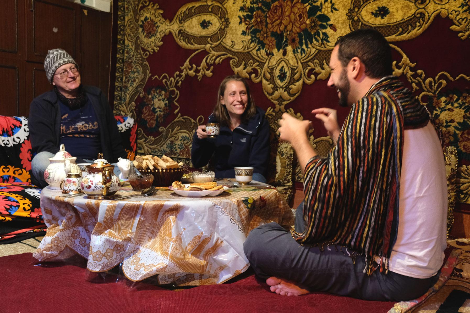 Thomas und Leo sitzen mit einem Mann um einem Tisch in einem Pamirhaus.