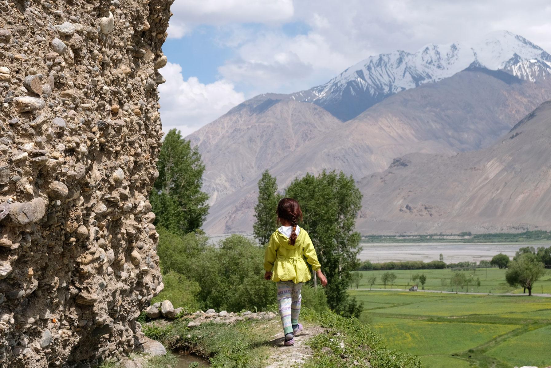 Ein Mädchen geht auf einem Pfad entlang einer Steinmauer.