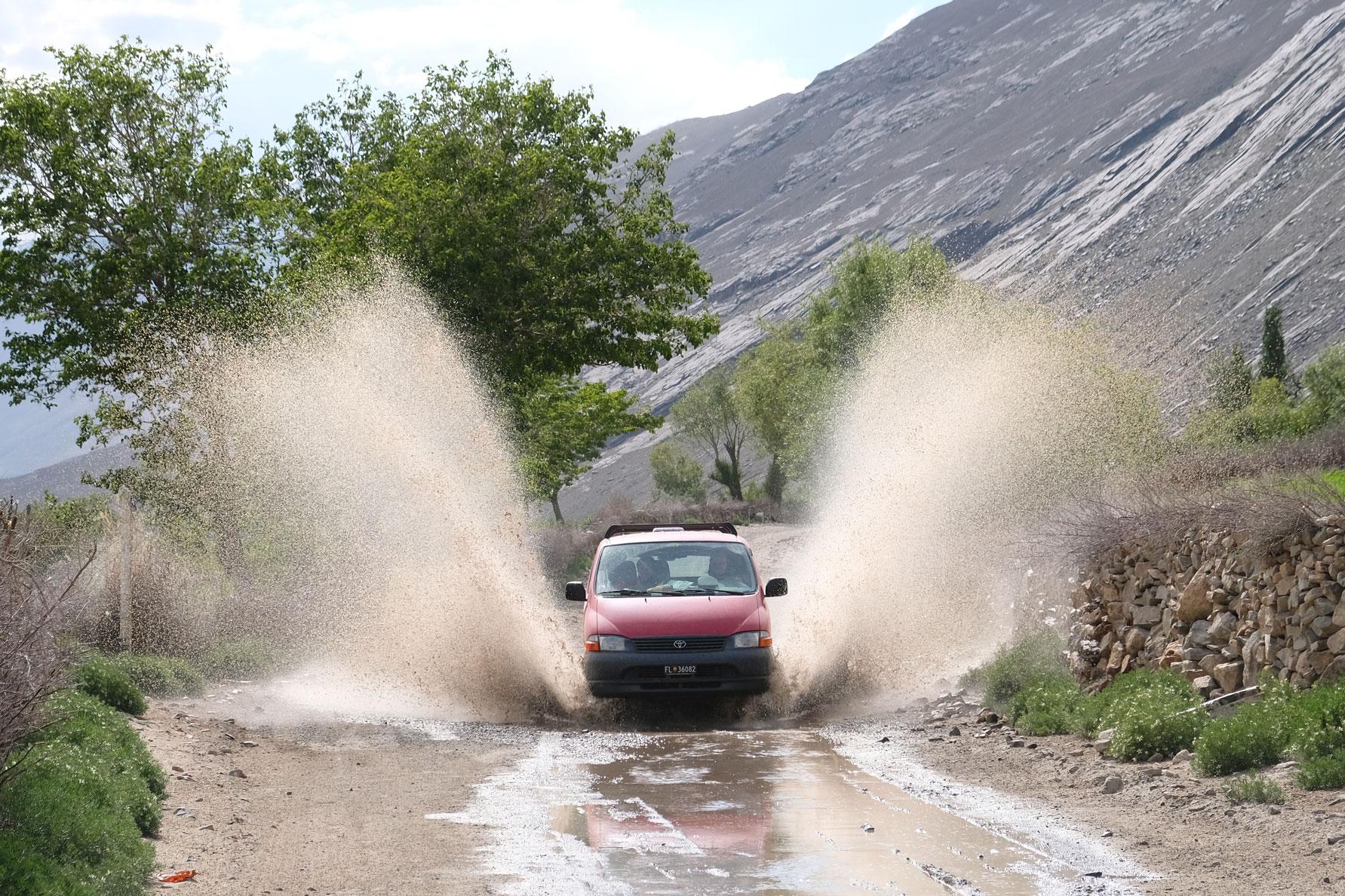 Ein roter Kleintransporter fährt durch eine Pfütze auf dem Pamir Highway.