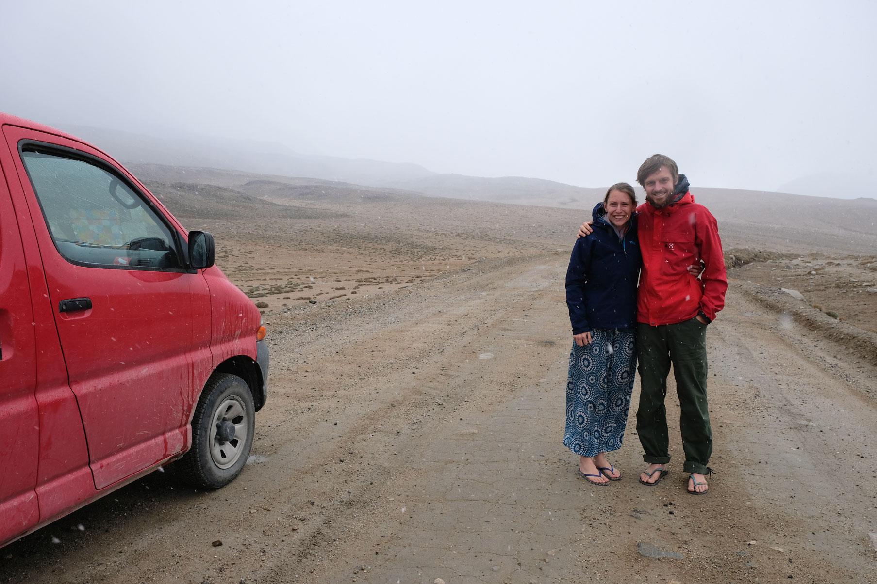 Leo und Sebastian stehen im Nebel neben einem roten Kleintransporter auf dem Kargush-Pass.