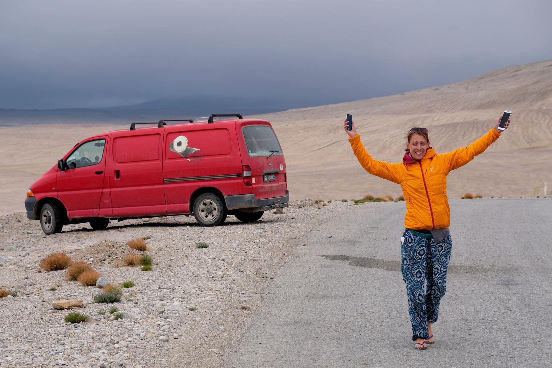 Leo hält zwei Handys in den Händen und streckt sich nach oben. Hinter ihr steht ein roter Kleintransporter am Straßenrand.