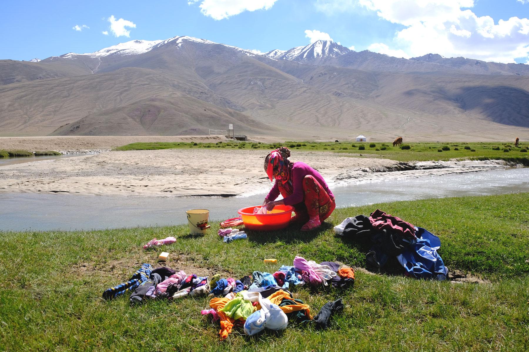 Eine Frau wäscht von Hand Wäsche an einem Fluss.