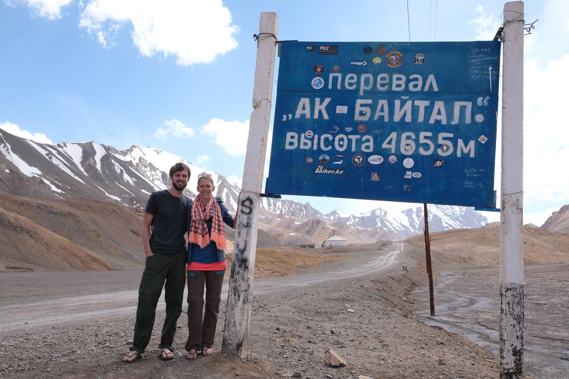 """Sebastian und Leo neben einem Schild, auf dem """"Ak Baital 4655 Meter"""" steht."""