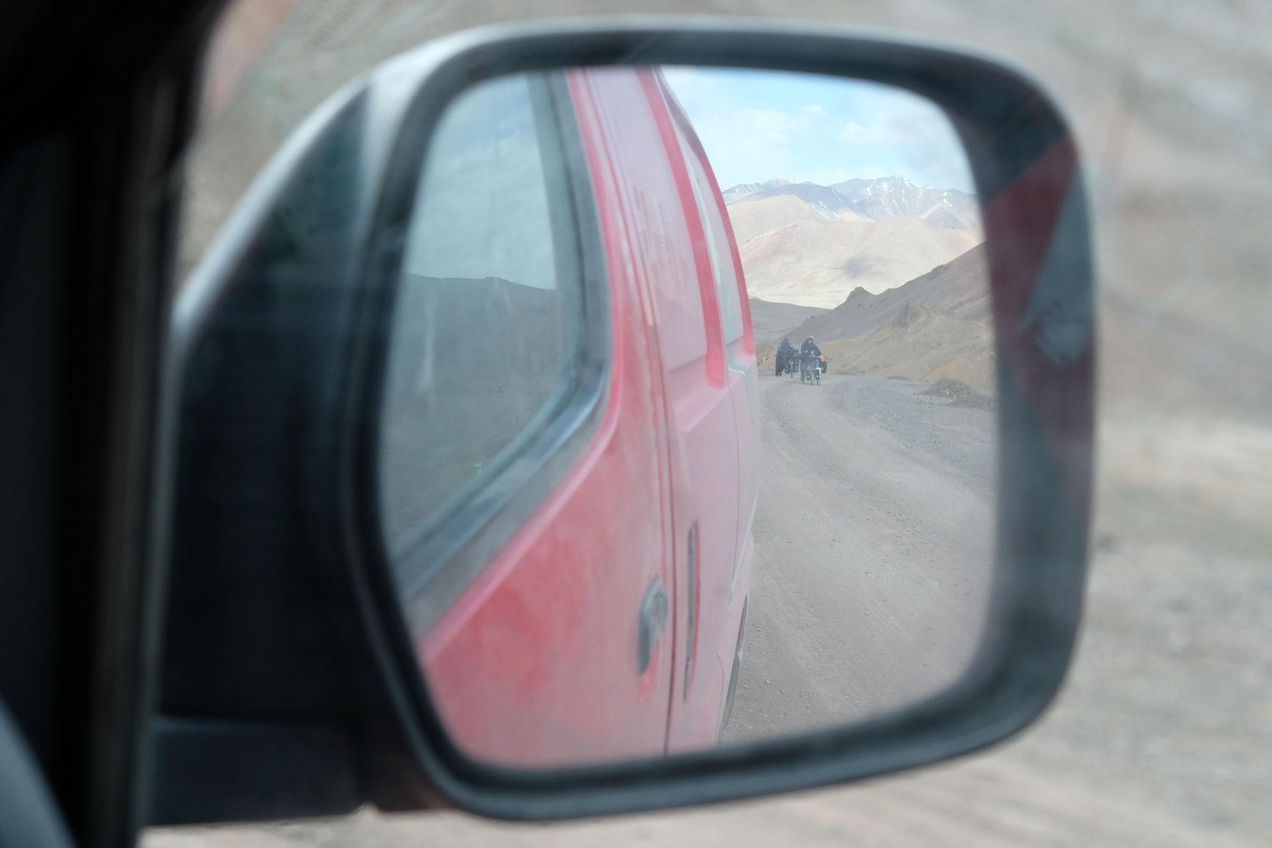 Rückspiegel eines Autos, in dem man zwei Radfahrerinnen sieht.