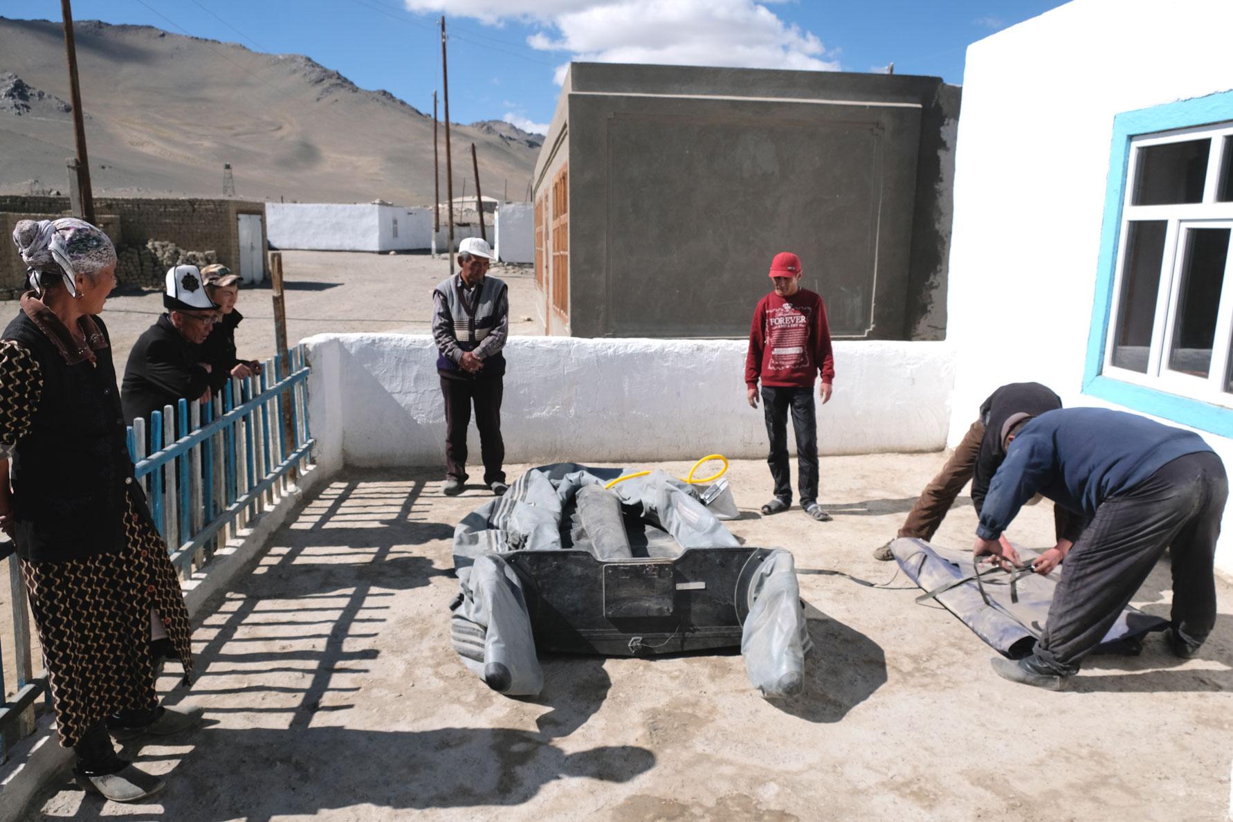 Zwei Männer bauen vor einem Haus ein Schlauchboot auf.