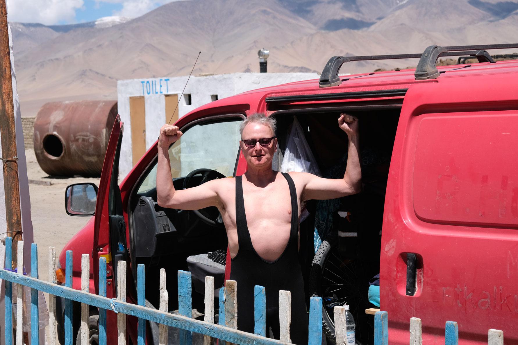 Thomas in einem knappen Schwimmanzug vor einem roten Kleintransporter.