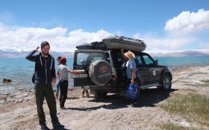 Sebastian am Karakul See vor einem Geländewagen, auf dessen Dach ein Schlauchboot ist.