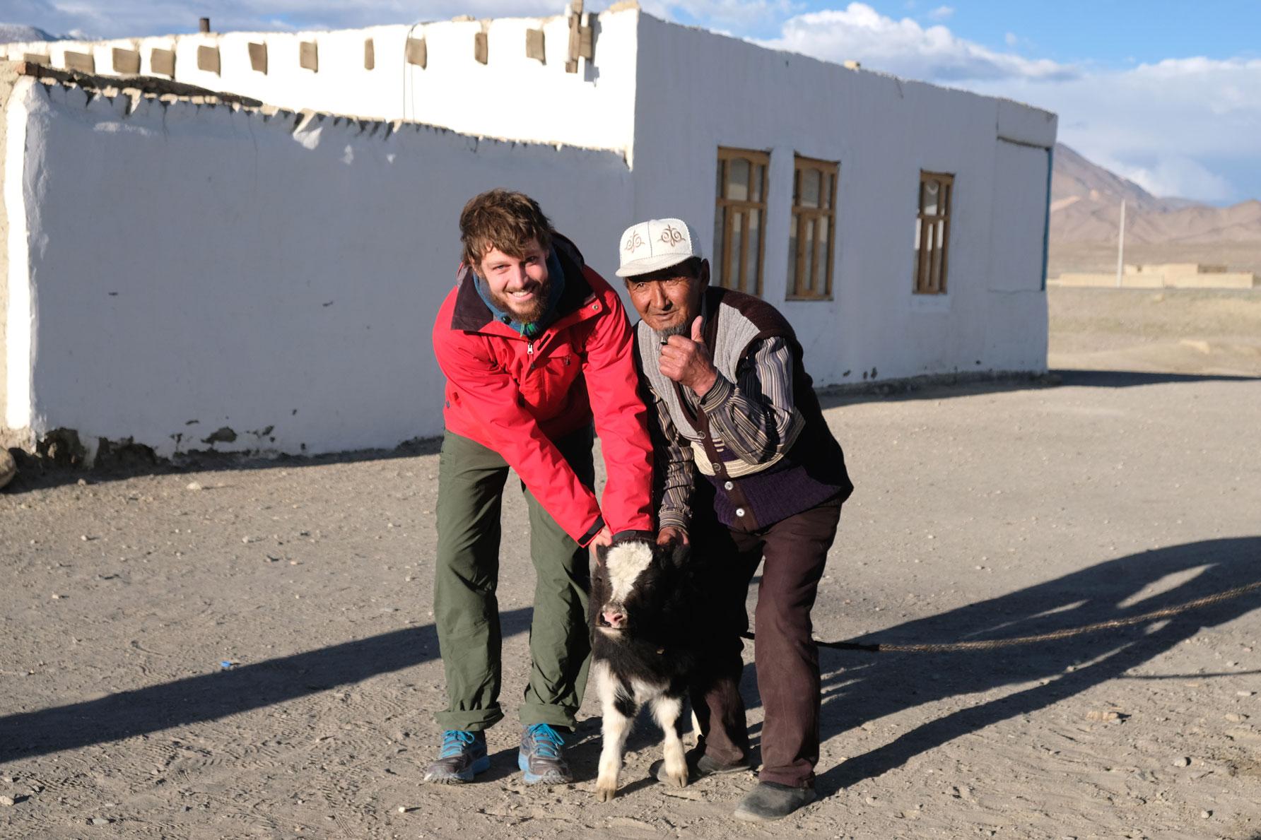 Leo und ein Mann halten ein junges Yak.