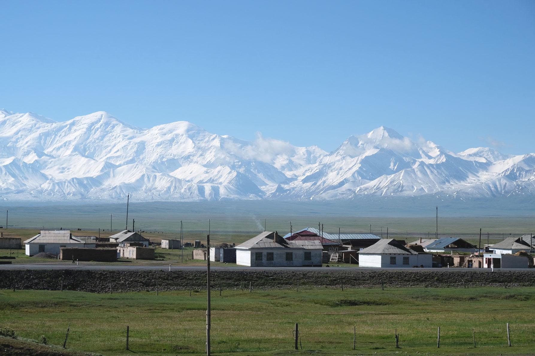 Sary Tasch in Kirgistan. Im Hintergrund ein schneebedecktes Gebirge.
