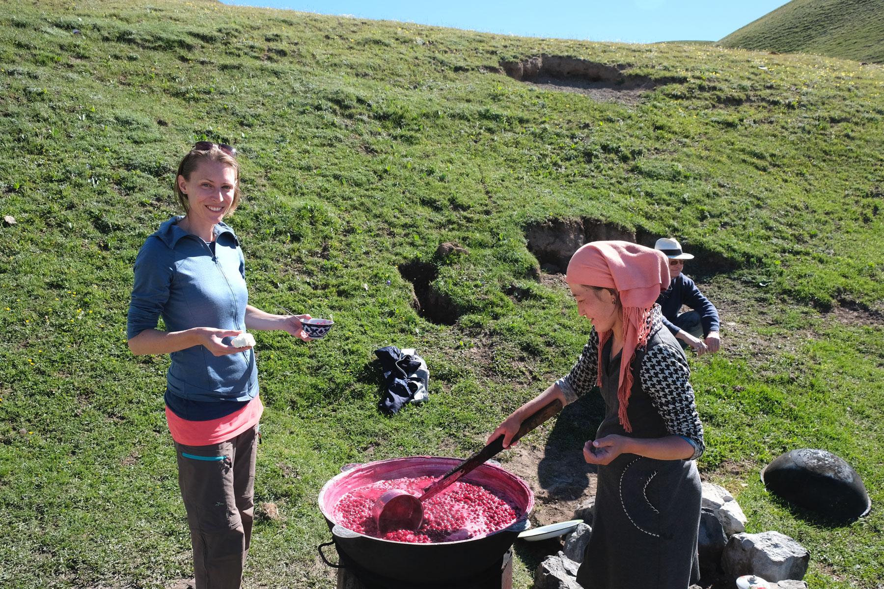 Leo steht neben einer Frau, die auf einer Wiese Kirschmarmelade kocht.